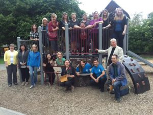 Group of 20 volunteers posed on a playground structure all facing the camera and smiling